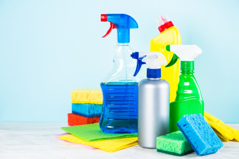 Pile of cleaning products, bottles, and sponges.