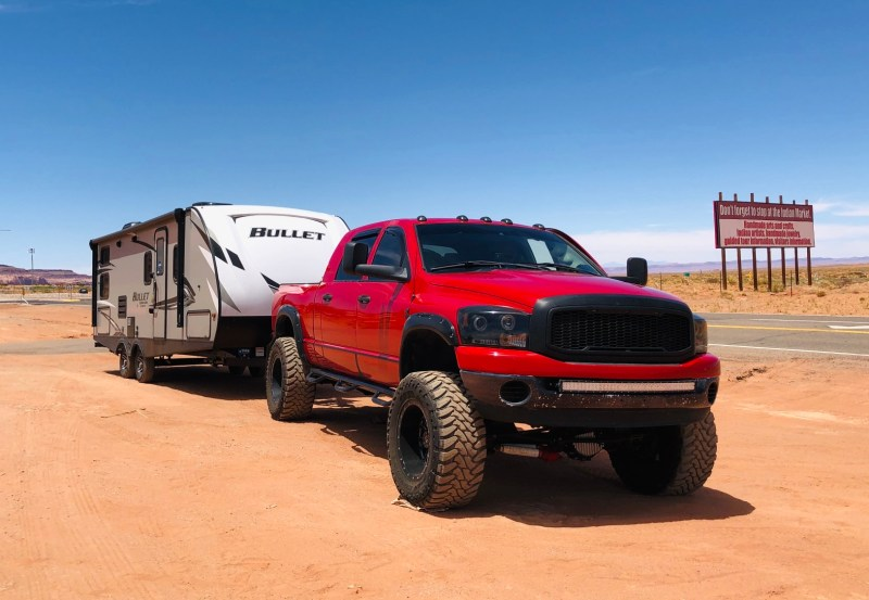 Red truck towing RV.