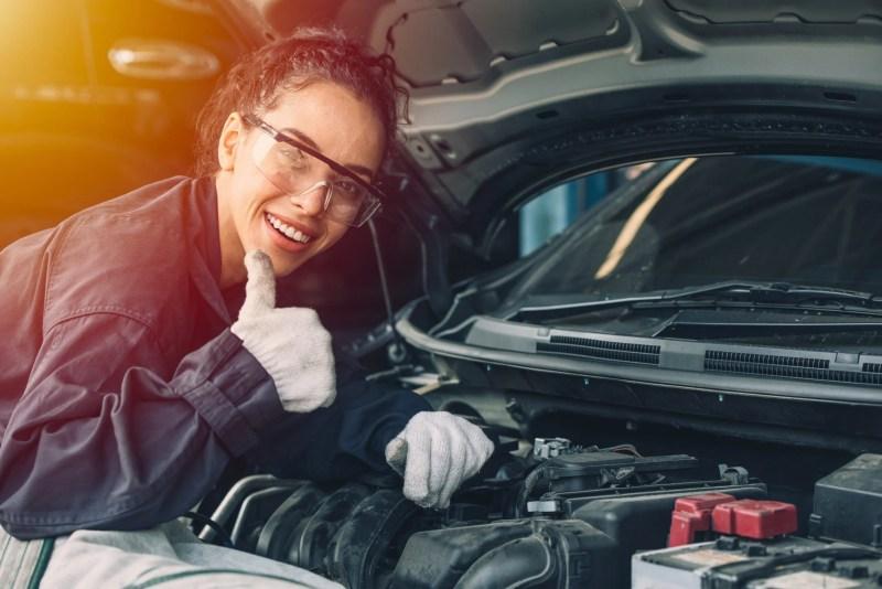 Woman mechanic fixing dead battery.