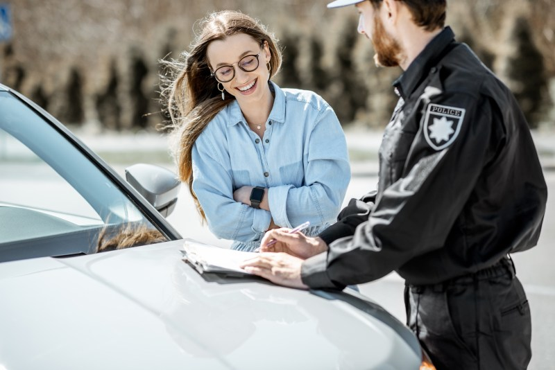 Woman talking to a police officer with car.