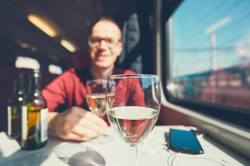 Man drinking wine in a moving vehicle.