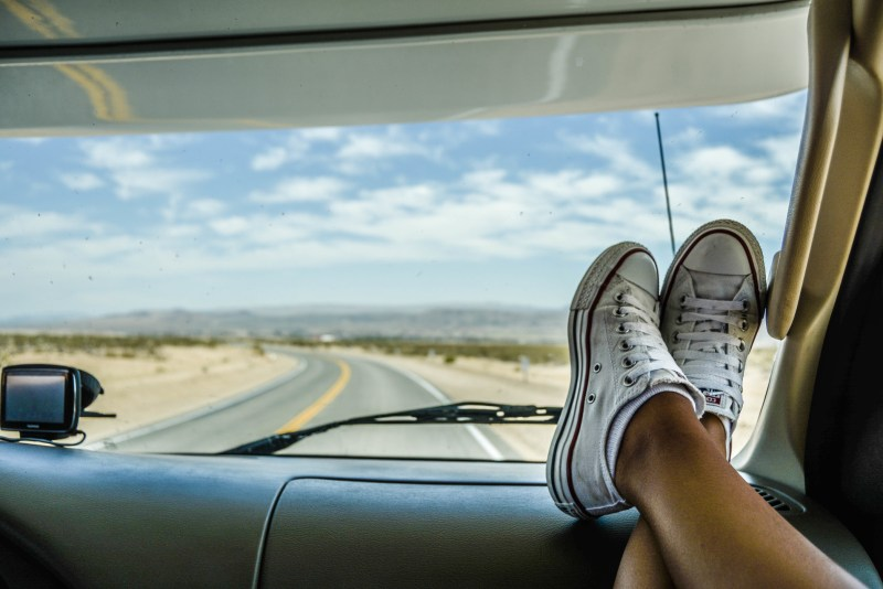 Woman feet up on dash while driving on highway.