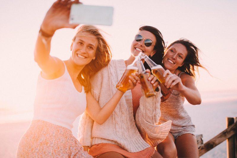 3 woman cheersing their beers.