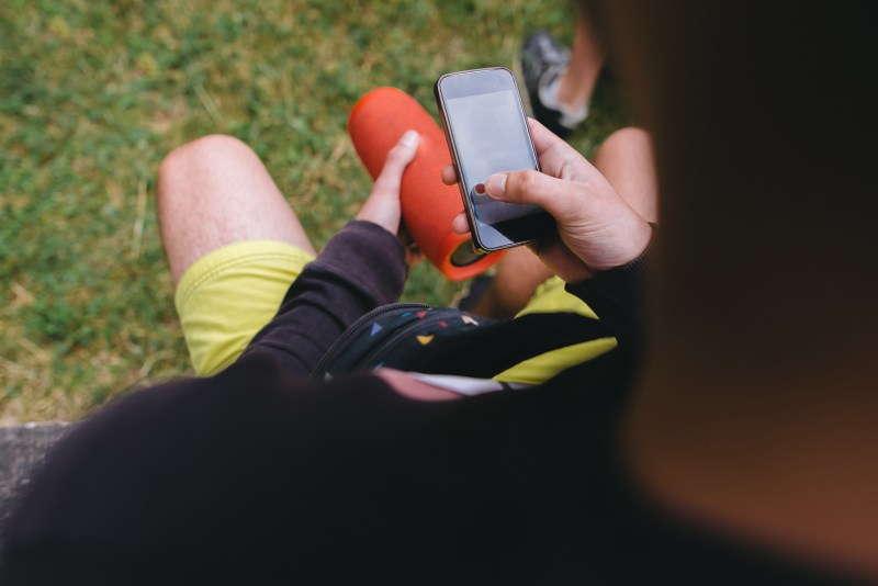 Man listening to music on portable speaker.