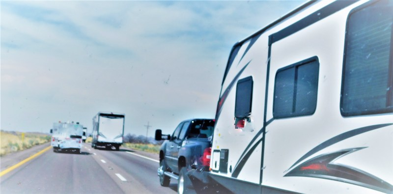 Truck towing RV down highway.