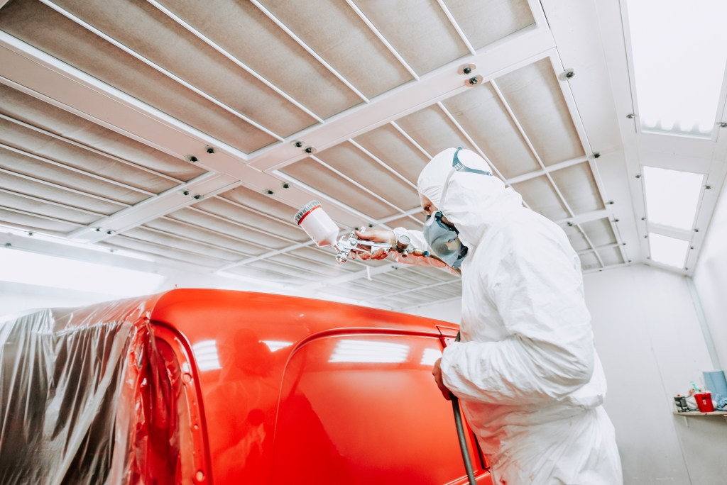 Auto mechanic painter painting a van red.
