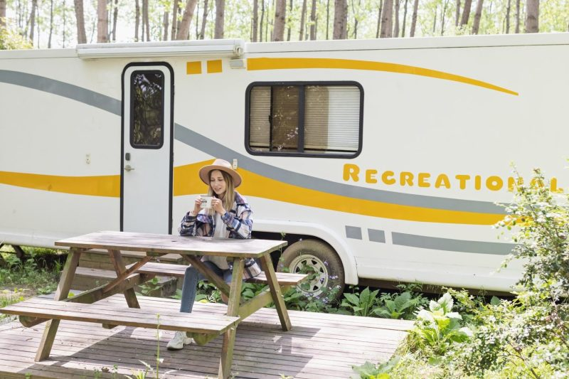 Woman sitting drinking coffee in front of her RV