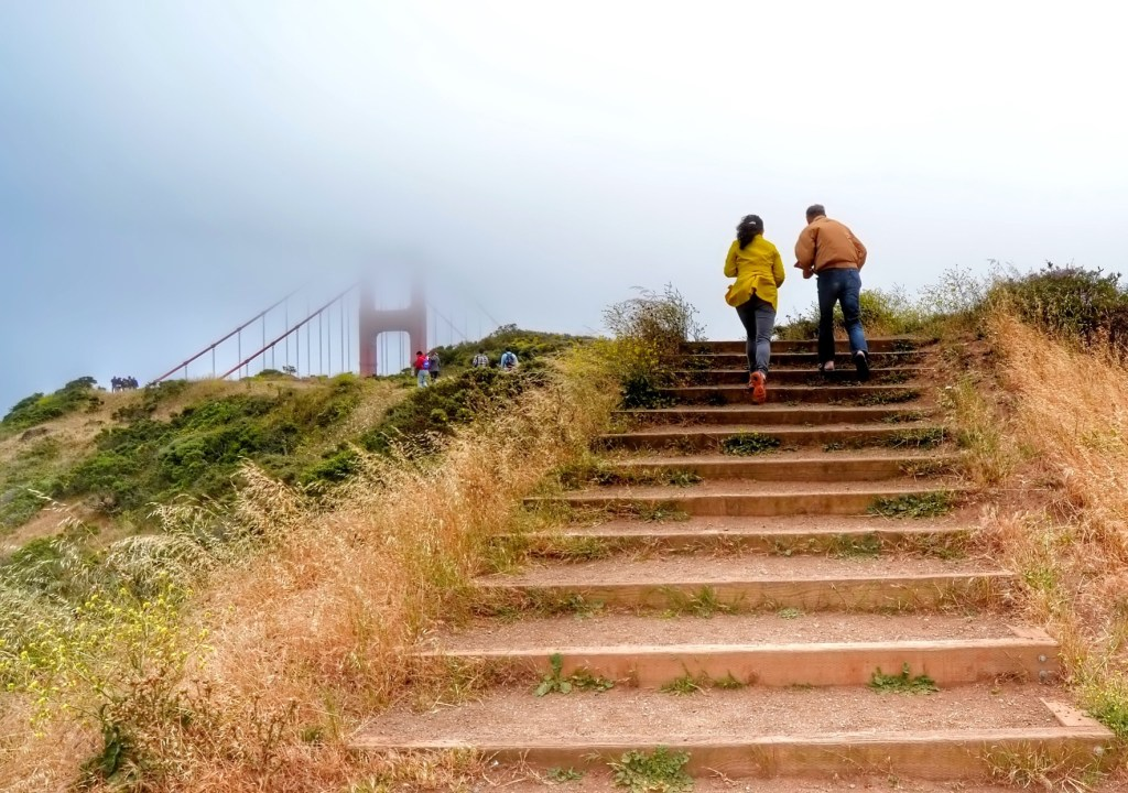 Couple hiking up stairs to the Golden Gate Bridge.