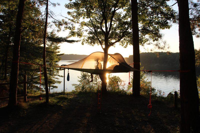 Man sitting in hammock tent in Northern Michigan