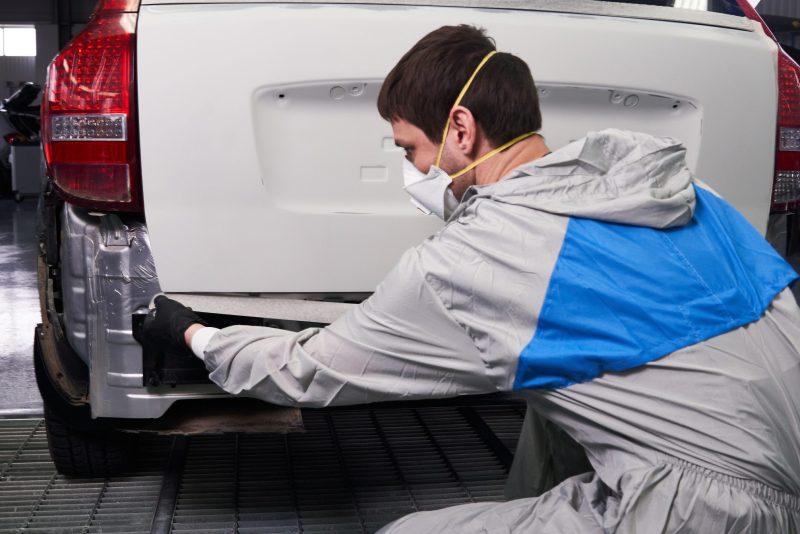 Man using tape to repair truck.