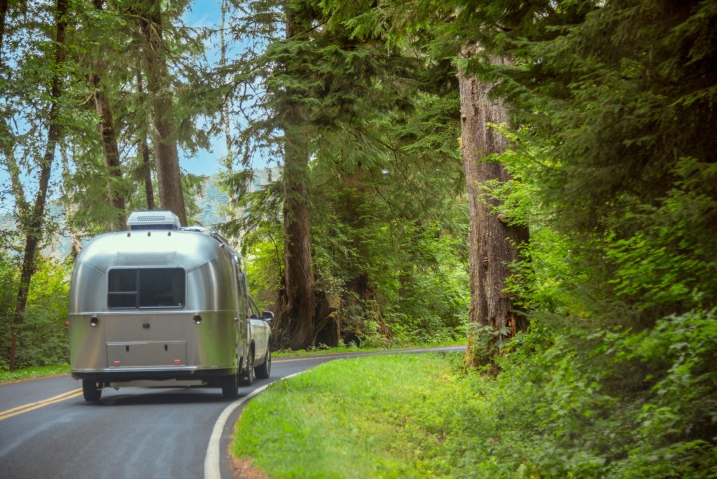Airstream being towed through the forest.