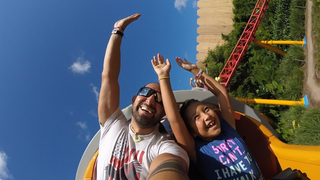 Father and daughter riding rollercoaster in Disney.