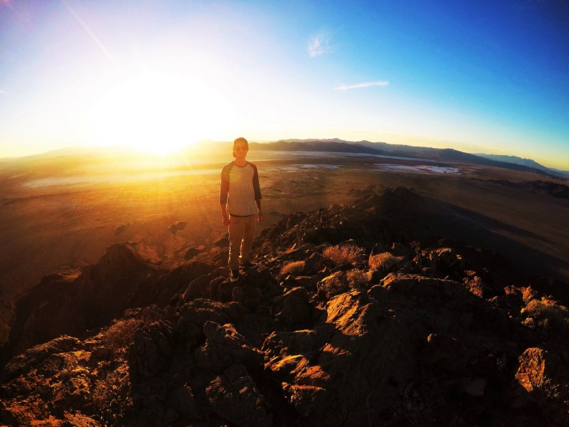 Man hiking along in Mojave National Preserve at sunset.