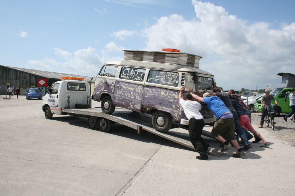 Men loading camper van onto tow truck.