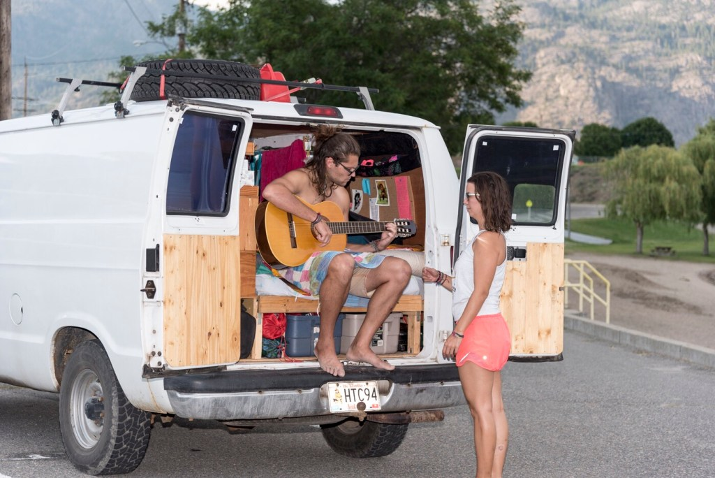Couple in campervan playing guitar.