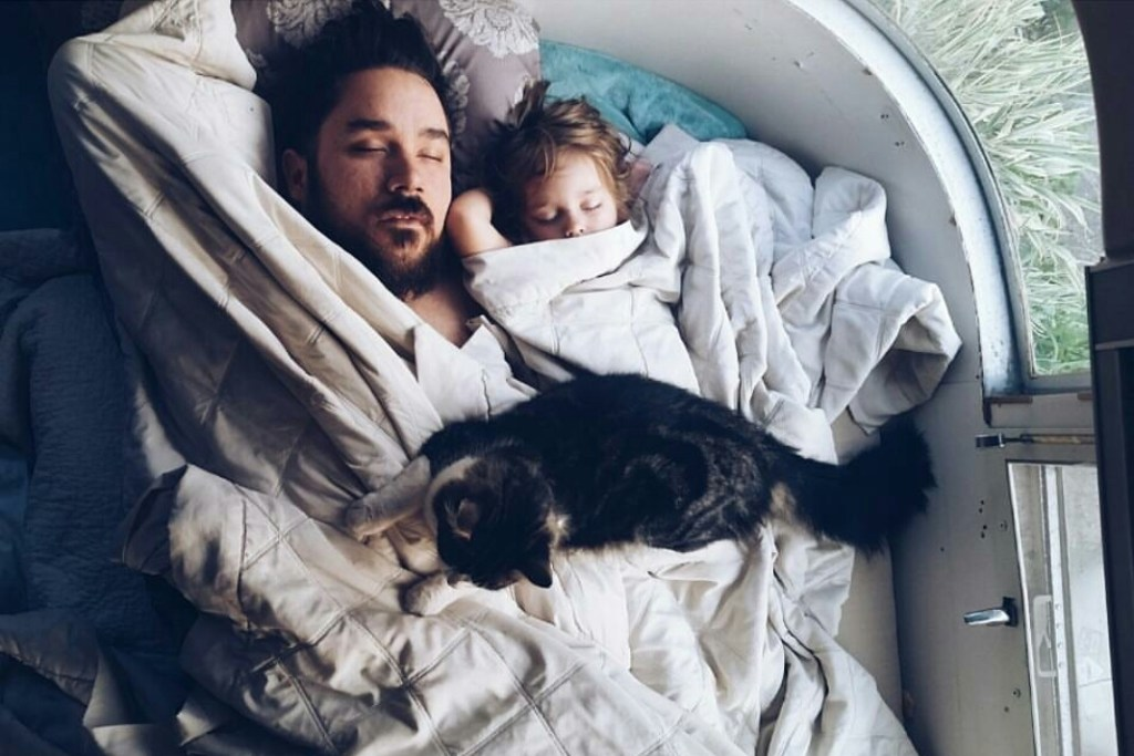 Dad, daughter, and cat sleeping in RV.