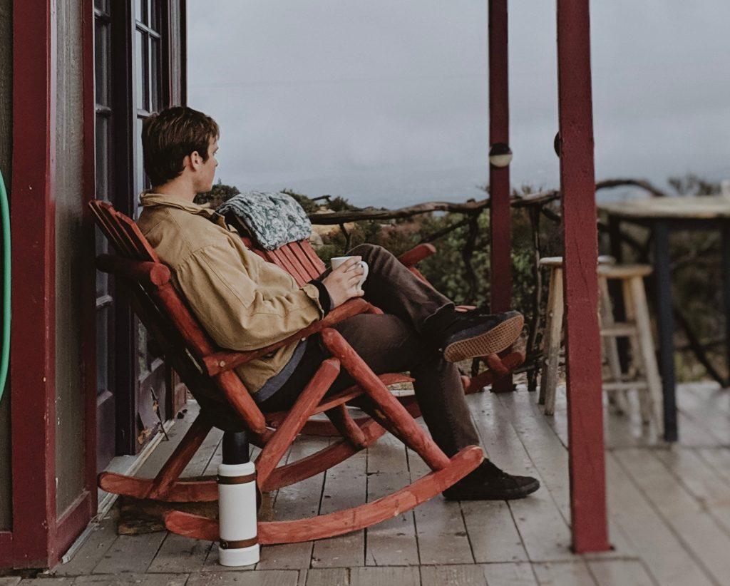 Man sitting on a rocking chair drinking coffee.