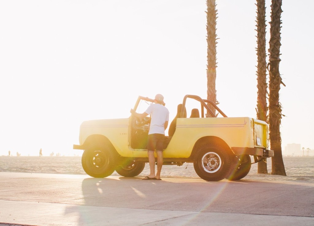 Man posing on beach next to his International Harvest Scout.