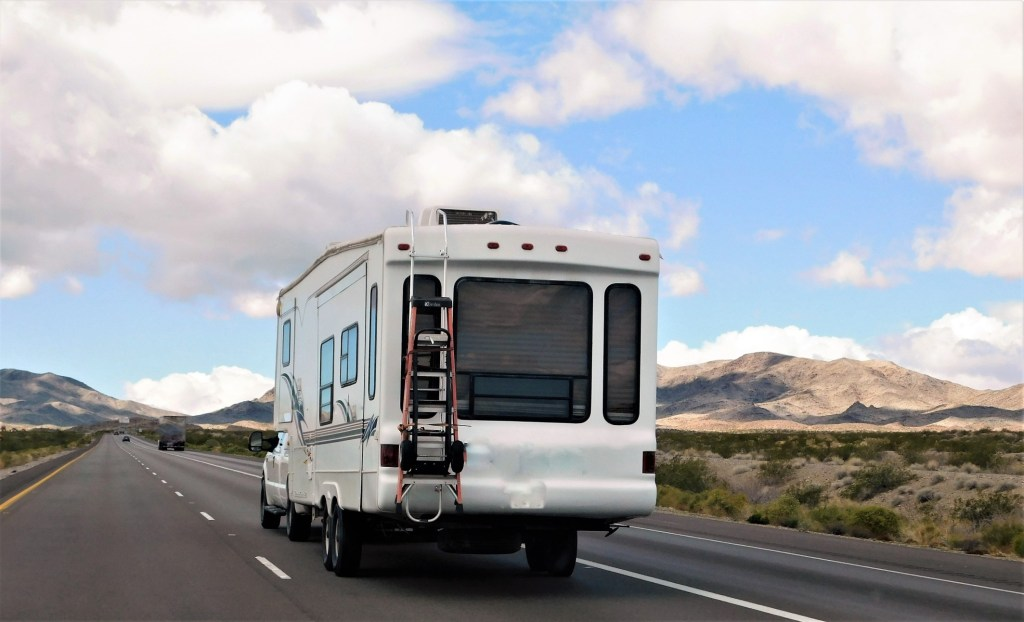 Fifth wheel RV driving down highway.