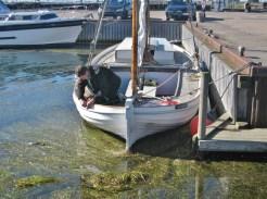 Niels Normand skruer det nye havneskilt fast