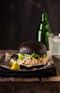 salmon burger on a black brioche bun with crunchy greens