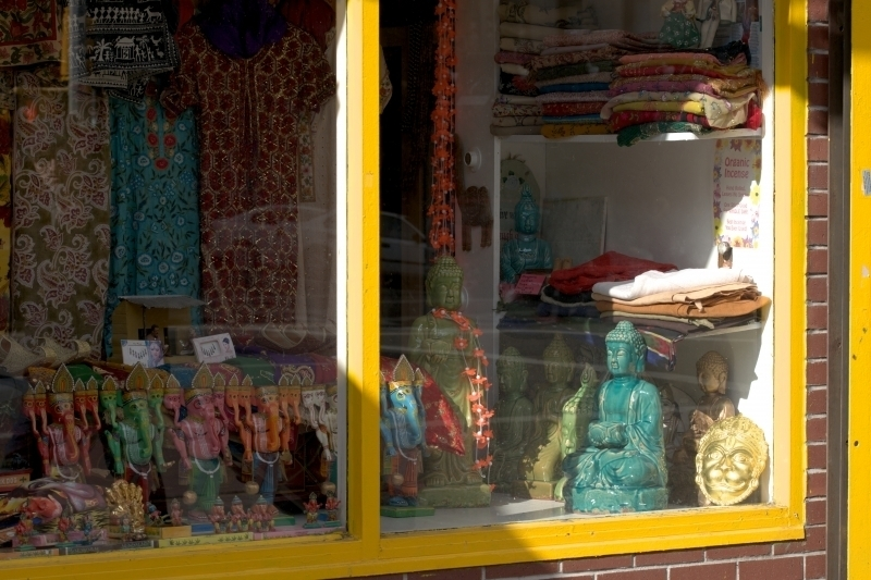Photograph of storefront selling statues of Buddha and Indian fabric, taken for healing by a medical doctor