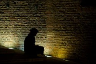 Photograph of black silhouette of seated person against illuminated brick wall at night, taken for healing by a medical doctor