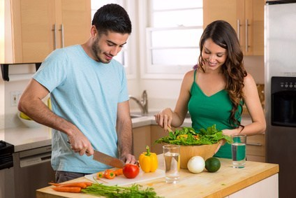 Couple happily preparing a salad together in the kitchen to represent the blog How to Succeed in the new relationship?