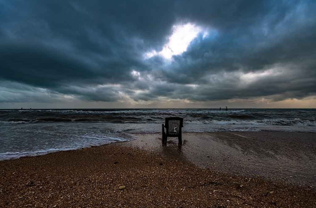 broken raggedy chair sitting on a sandy beach in the direction of the ocean.