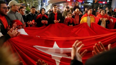 People of the Turkish community living in Germany pray as celebrating on Kurfuerstendamm boulevard on the outcome of Turkey's referendum on the constitution, in Berlin