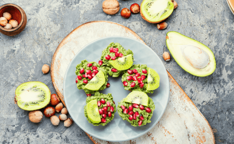 avocados with kiwi and pomegranate seeds on plate by dr michele ross