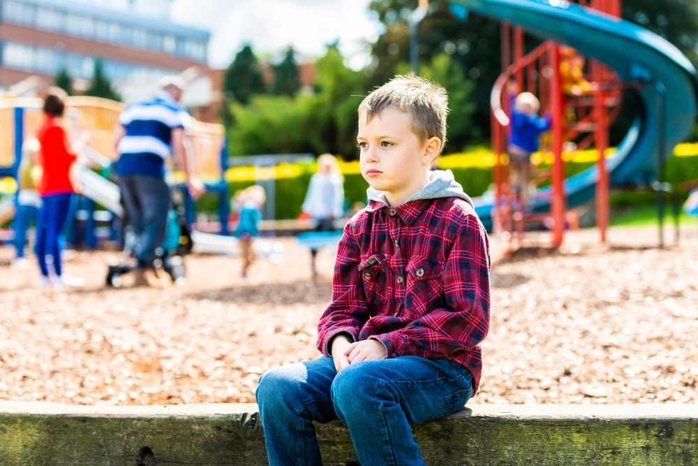 young white boy with ADHD sitting alone at playground