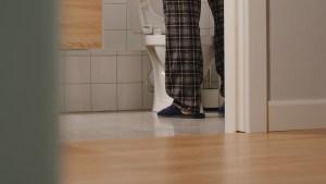 man walking to toilet in pajama pants