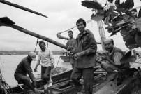Những ngư dân này đang vá víu lại con thuyền rách nát These fishermen are repairing their wrecked boats after storm