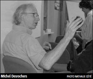 On voit Michel Desrochers de côté, presque de dos, bougeant les bras en parlant. Il semble être dans un local communautaire.