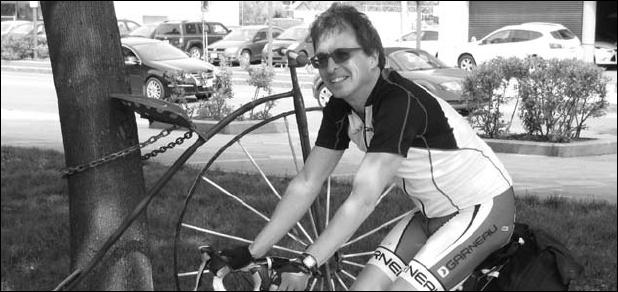 Photo de M. Côté sur son vélo, souriant, lunettes de soleil. À côté de lui un ancien vélo de type roue géante. Des voitures visibles derrière plus loin.