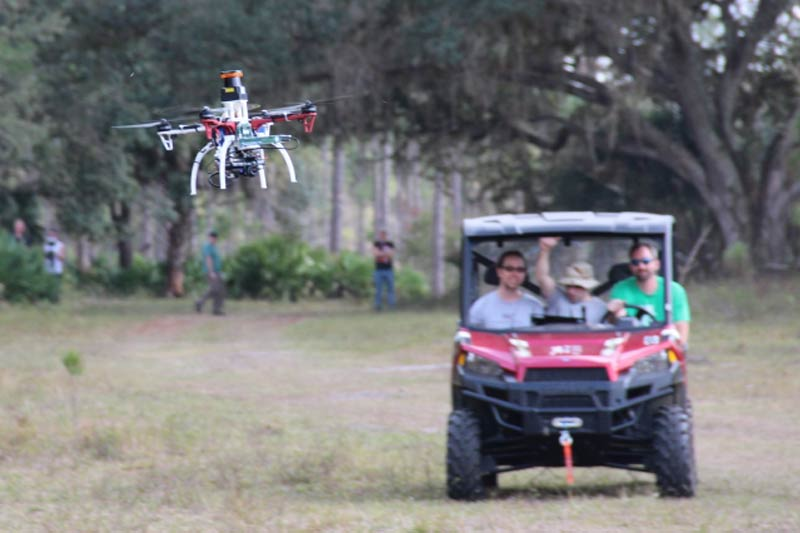 Researchers trail a drone on a test flight outdoors