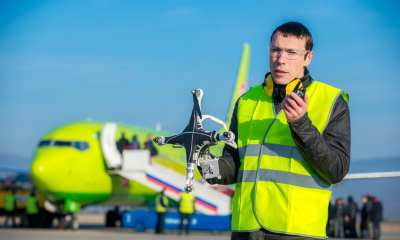 An airport worker holding crashed quadcopter near airliner   Mark Agnor