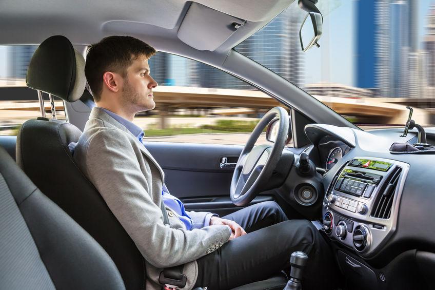A young man sitting inside an autonomous car