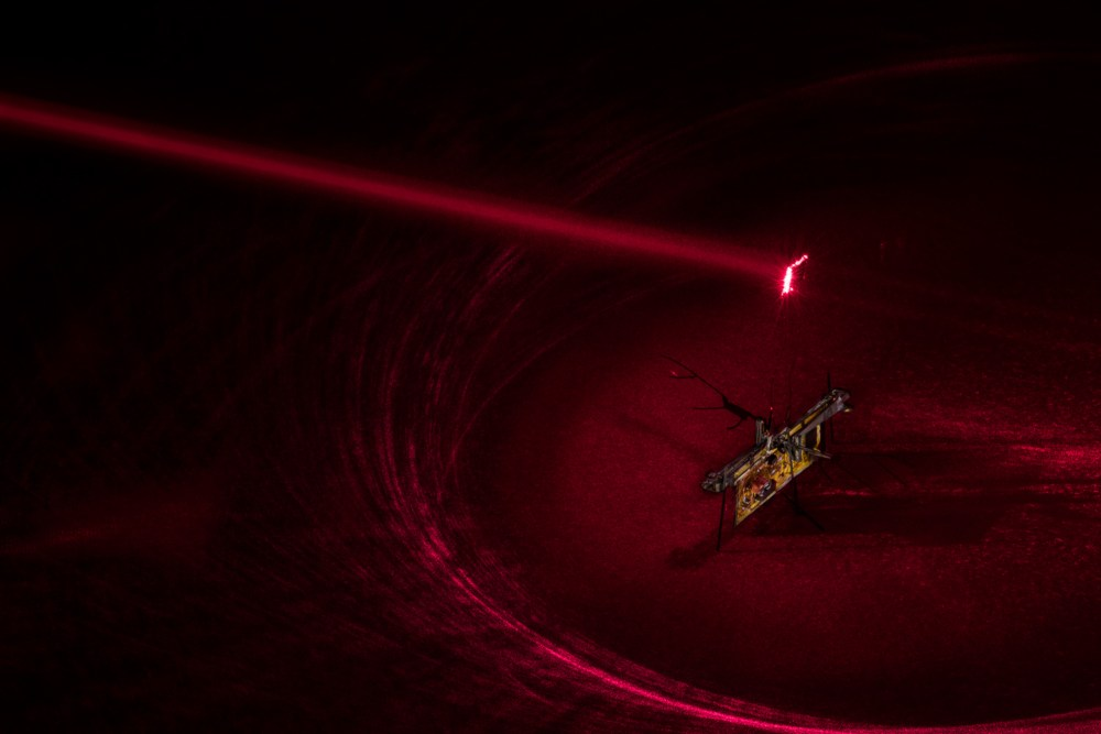 To power RoboFly, the engineers pointed an invisible laser beam (shown here in red laser) at a photovoltaic cell, which is attached above the robot and converts the laser light into electricity.Mark Stone/University of Washington