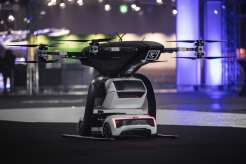 """At Drone Week in Amsterdam Audi, Airbus and Italdesign are presenting for the first time a flying and driving prototype of """"Pop.Up Next"""". This innovative concept for a flying taxi combines a self-driving electric car with a passenger drone. In the first public test flight, the flight module accurately placed a passenger capsule on the ground module, which then drove from the test grounds autonomously. This is still a 1:4 scale model."""