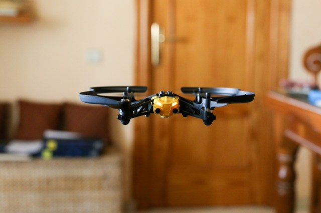 A black and orange drone flying indoors.