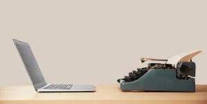 A slim laptop sits opposite a classic metal typewriter
