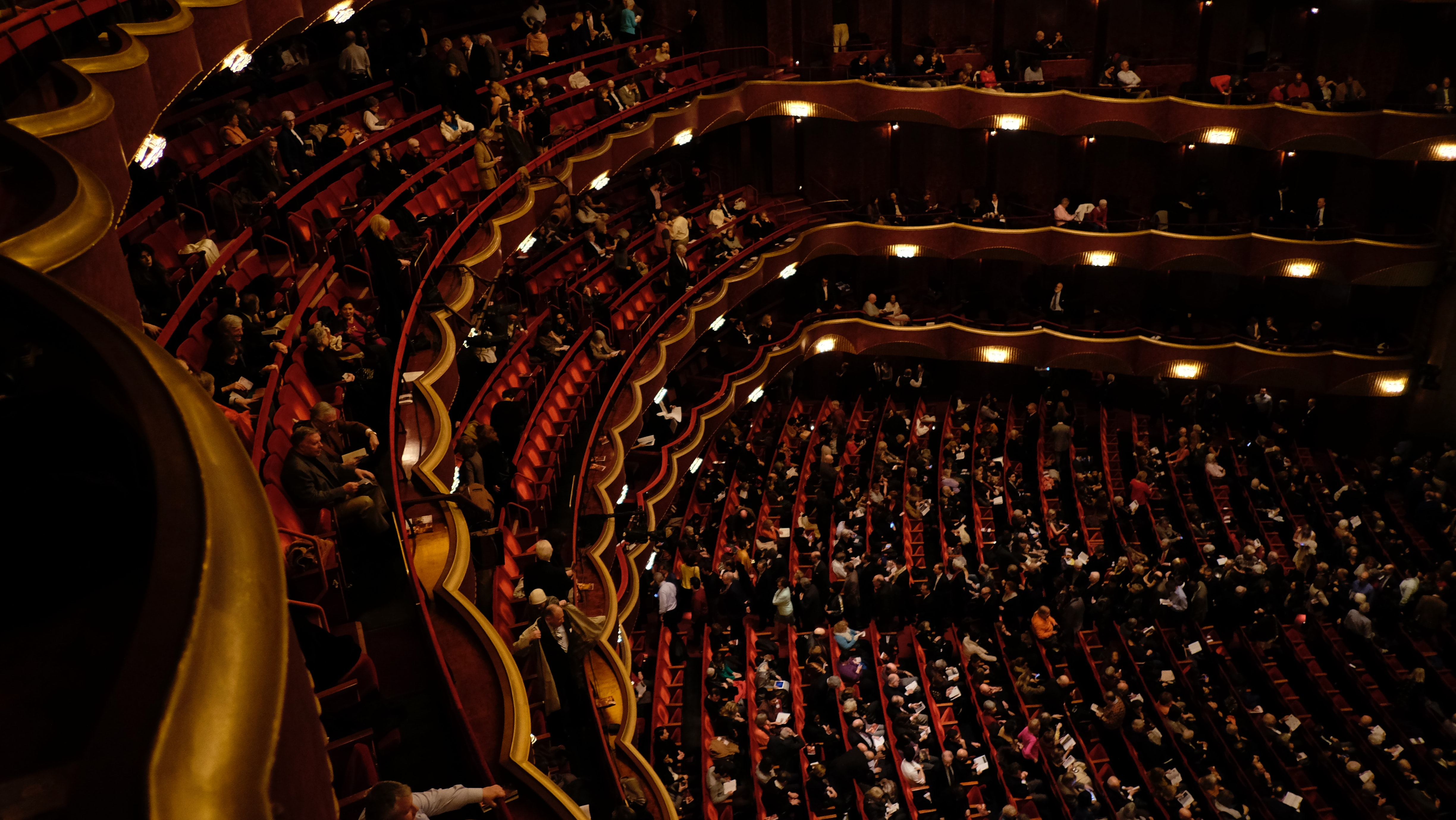 A performance venue with balcony tiers and orchestra floor filled with audience in red seats under soft lighting.