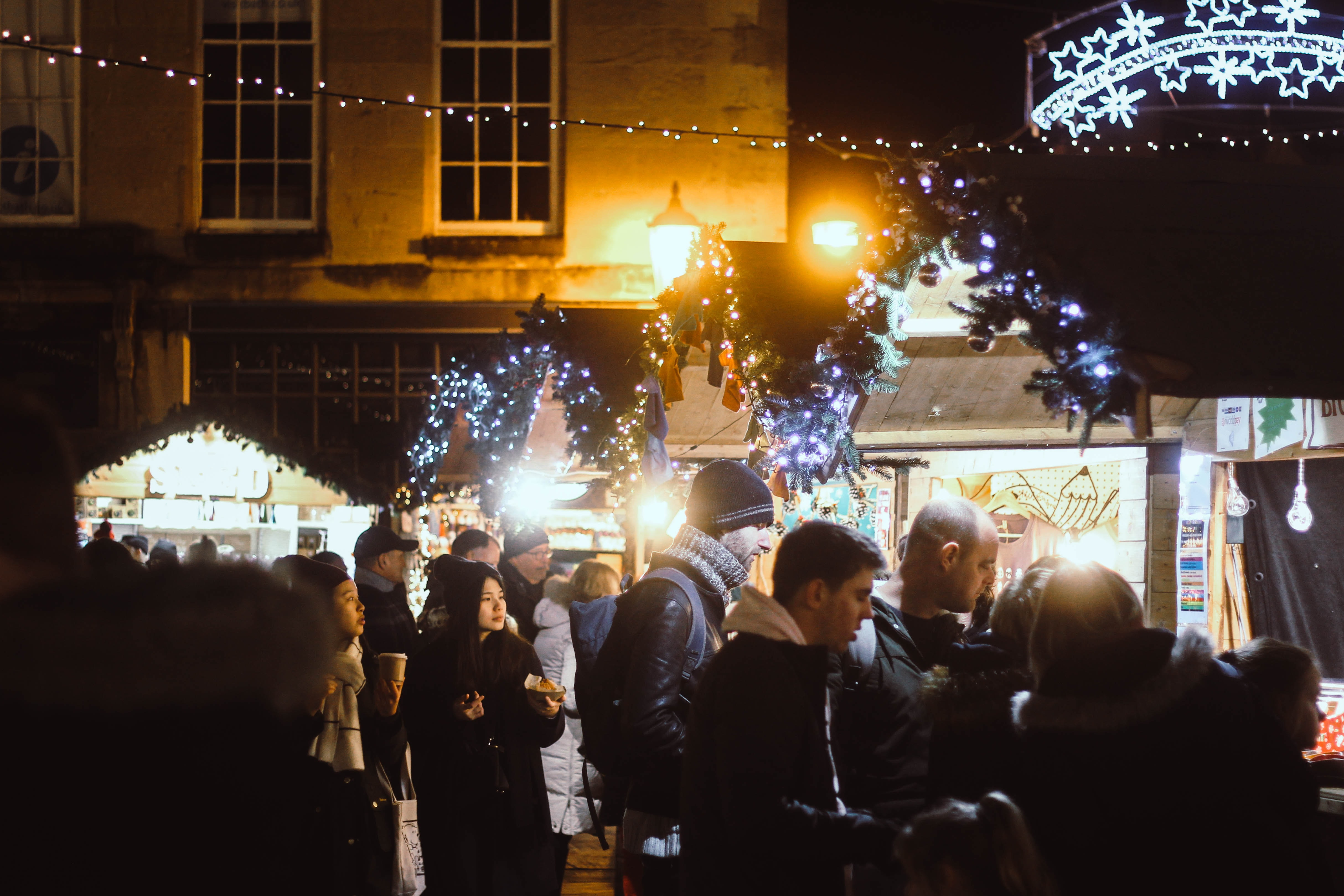 Shoppers browse the outdoor Christmas Marketing in Bath, UK at night under twinkle lights and Georgian buildings.