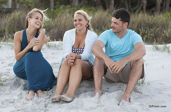 Three friends sit on the beach talking at sunset