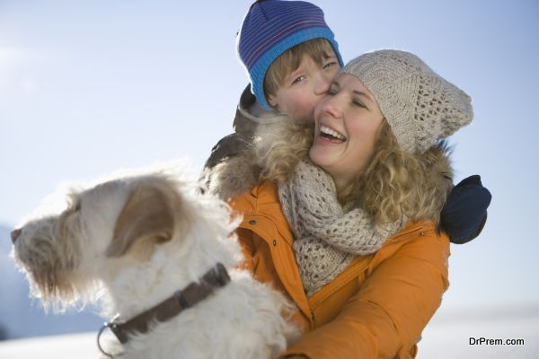 Mother laughing with son and pet dog in snow