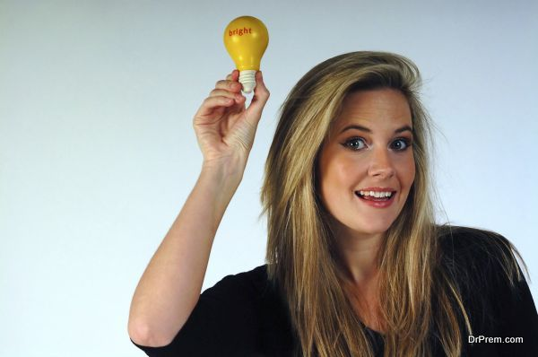 Young woman holding aloft a lightbulb.