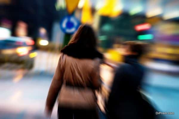 Two attractive women walking in a big city centre at night