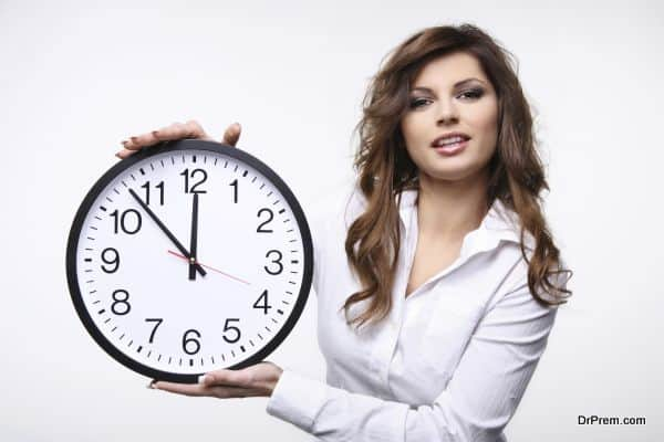 Beautiful smiling woman holding big clock.